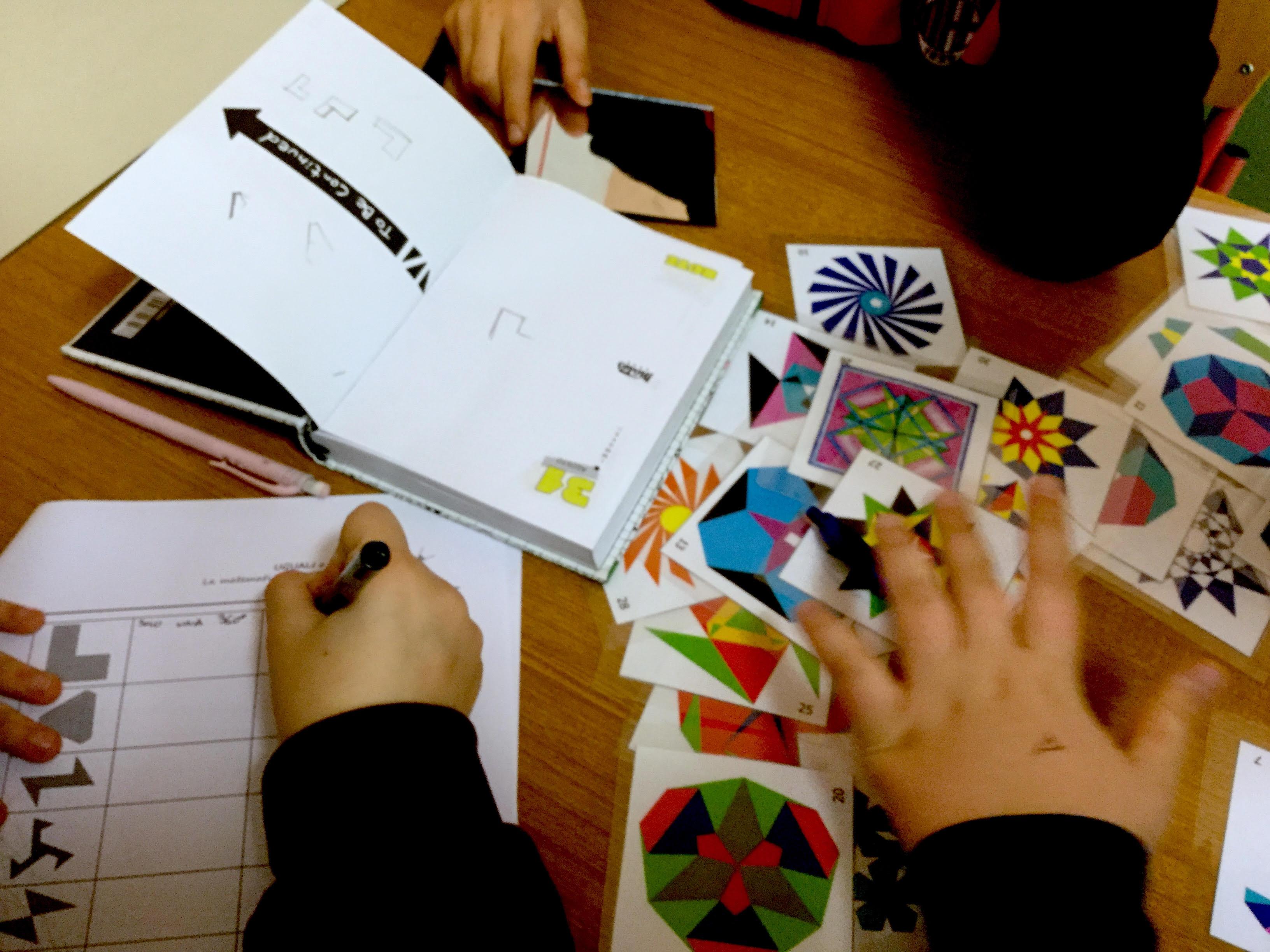 ragazzi che studiano la simmetria di alcune figure, per classificare i rosoni tra esse presenti
