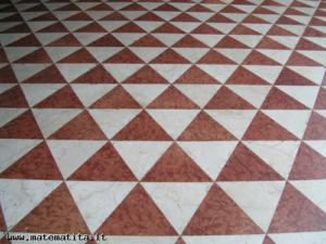 Una pavimentazione con mattonelle a forma di triangoli equilateri, sei in ogni vertice (Milano, corso Vittorio Emanuele). Il mondo degli angoli e dei poligoni incontra quello delle frazioni, grazie a un ponte tra aritmetica e geometria.