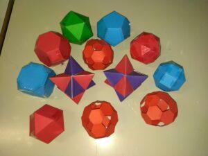 """Modelli di poliedri costruiti con cartoncino. Il problema """"Prismi, piramidi e altro"""" fa da ponte tra geometria, aritmetica, algebra e topologia."""